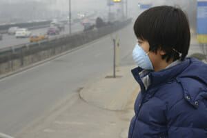 Boy wearing mouth mask against air, istock photo